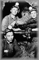 Three men in an underground shaft around a drill, wpH434